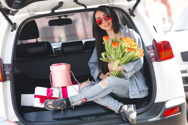 Портрет молодой красивой женщины весной держит букет свежих цветов.