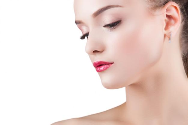 美しさの肖像画。若い美しいブロンドの女性。白の魅力的な女性。女性が化粧をする