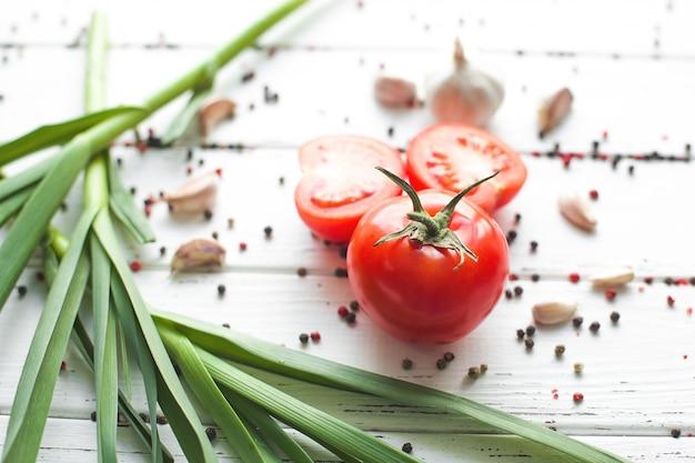 Свежие помидоры со специями. органическая здоровая еда на деревянном зеленом чесноке. летние и осенние овощи.
