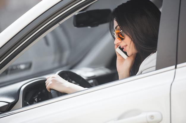 Женщина водитель разговаривает по телефону. красивая девушка в машине. леди за рулем белой машины.