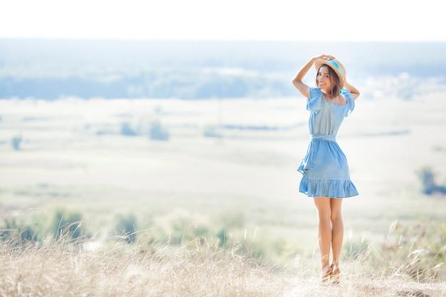 Молодая женщина на природе свобода. женщина свободна. дама восхищается удивительным естественным видом. женщина восхищается пейзажем.