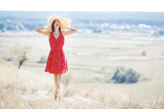 ジューシーな夏または秋の屋外で若い美しい女性の肖像画落下時間の女性。赤いスタイリッシュなドレスを着て自然の女性。