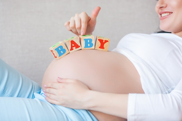 Молодая беременная женщина в помещении. макрофотография портрет женщины ожидали. красивая женщина ждет своего маленького ребенка на рождение.