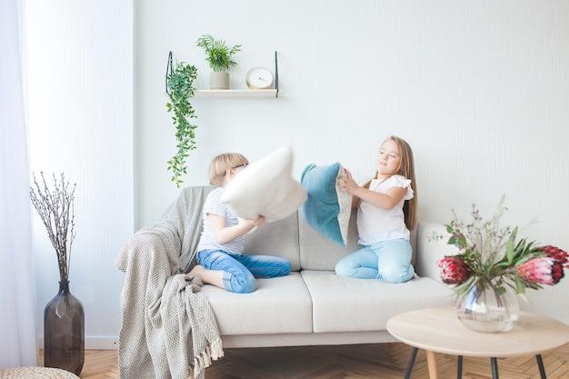 屋内で楽しんでいる小さな子供たち。ソファで遊ぶ子供たち。枕投げ。兄と妹が家で混乱しています。