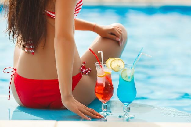 カクテルと水着のスイミングプールで休んで若いかなりスリムな美しい少女。リラックスして日焼けする陽気な女性。スイミングプールのお尻。認識できない女性