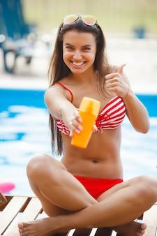 スイミングプールの日焼け近くの完璧な女性。日光浴を持つ美しい少女。ビーチでリラックスしたきれいな女性