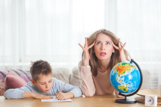 若い母親が自宅で彼女の幼い息子を教えています。ママと彼女の子供は屋内で地理を勉強しています
