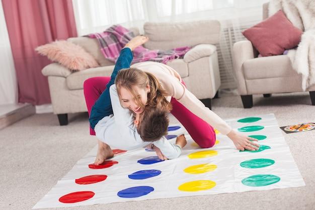 若い母親が彼女の息子とツイスターを演奏します。屋内で陽気な家族。一緒に遊んで幸せな家族