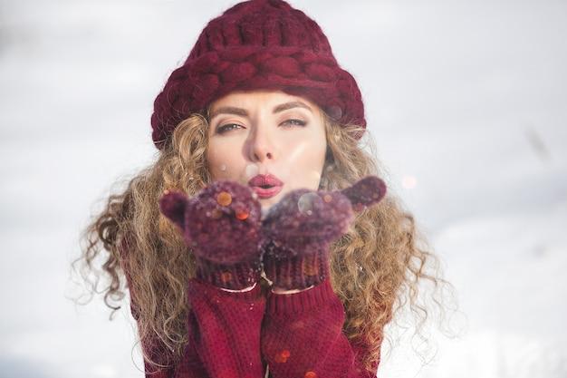 Портрет молодой жизнерадостной женщины дует снег