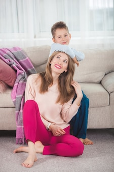 若い母親は彼女の息子とアクティブなゲームをプレイします。屋内で楽しんでいる陽気な家族。