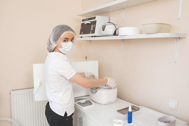ネイリストは、オートクレーブまたはオーブンでツールを滅菌します。マスターは、消毒のために彼女の器具を準備するサロンです。