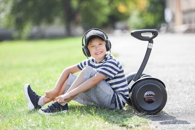 Улыбка ребенка езда на сегвее. активная молодежь. милый мальчик на открытом воздухе с электрическим вездеходом.