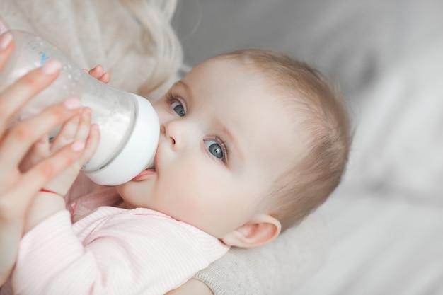 若い母親は、子数式のボトルで彼女の小さなかわいい赤ちゃんの娘を供給します。自宅で彼女の生まれたばかりの赤ちゃんを持つ女性。ママが子供の世話をしています。母乳育児の代替。