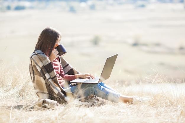 Молодая привлекательная женщина работает на ноутбуке на открытом воздухе. женщина делает ее независимую работу на пк. удаленный работник в отпуске.
