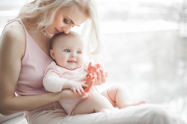 若い母親が彼女の小さな女の赤ちゃんの世話をします。美しいお母さんと娘の屋内の寝室。愛する家族。彼女の子供を保持している魅力的なママ。