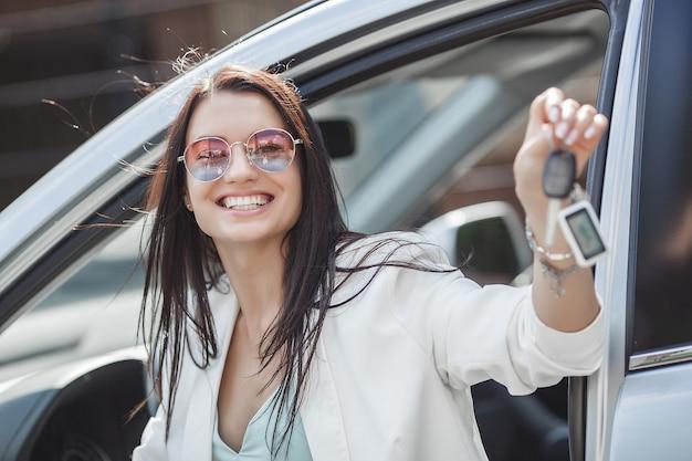 若い魅力的な女性はちょうど新しい車を買った。新しい自動車から女性保持キー。