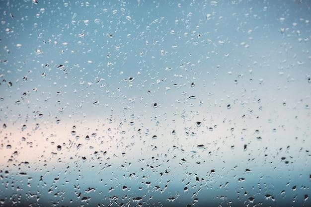 ウィンドウに雨の滴。ガラスの水。滴を実行しています。背景の概念。