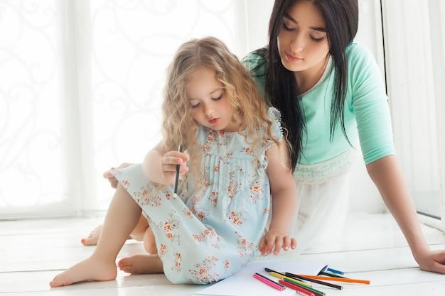 Маленькая милая дочь и ее мать, рисование красочными карандашами и с удовольствием вместе. милый ребенок и мама играя внутри помещения. счастливая семья, тратить время на рисование.