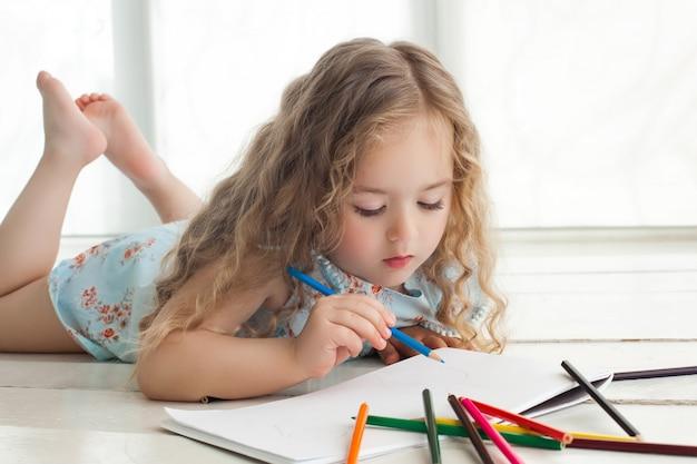 Милый рисунок маленькой девочки с красочными карандашами на бумаге. довольно маленький ребенок, рисование в помещении. прелестный художник