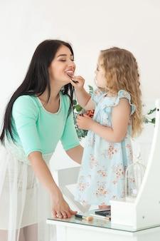 小さなかわいい娘と彼女の母親の申請がお互いを構成しています。かなり若いお母さんと愛らしい女の子が一緒に楽しんで。美しいファッショニスタファミリー