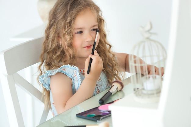 適用するかわいい女の子が鏡を見てメイクします。ファッショニスタの少女が母親の化粧品で遊んでいます。愛らしい子供屋内