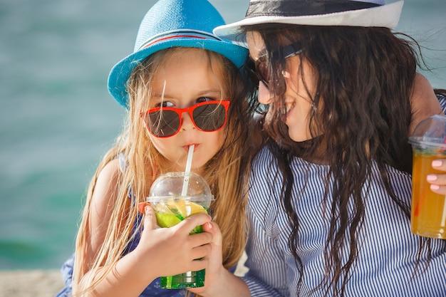 Молодая красивая мать и ее маленькая дочь на пляже, с удовольствием. девочки пьют лимонад.