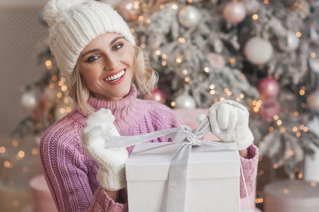 クリスマスシーンに若い魅力的な女性の肖像画を閉じます。クリスマスプレゼントボックスを開くと笑顔の美しい女性。