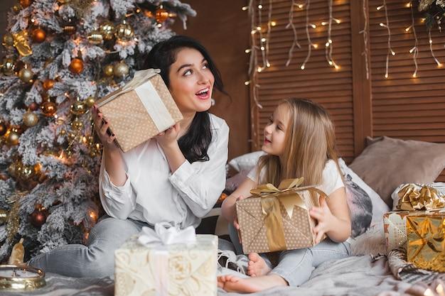 若いかわいい母親と彼女の小さな娘がクリスマスプレゼントを共有