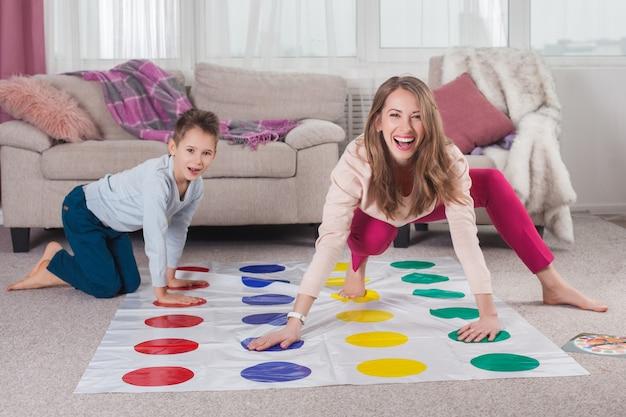若い母親が彼女の息子とツイスターを演奏します。陽気な家族屋内。一緒に遊んで幸せな家族