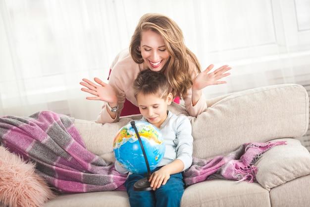 Молодая мама помогает сыну делать домашнее задание. семья выбирает, куда поехать в отпуск. мать и ее ребенок держит глобус