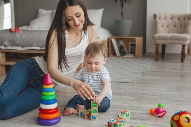 Молодая красивая мать, играя со своим маленьким сыном. веселая семья весело в помещении с маленьким маленьким сыном