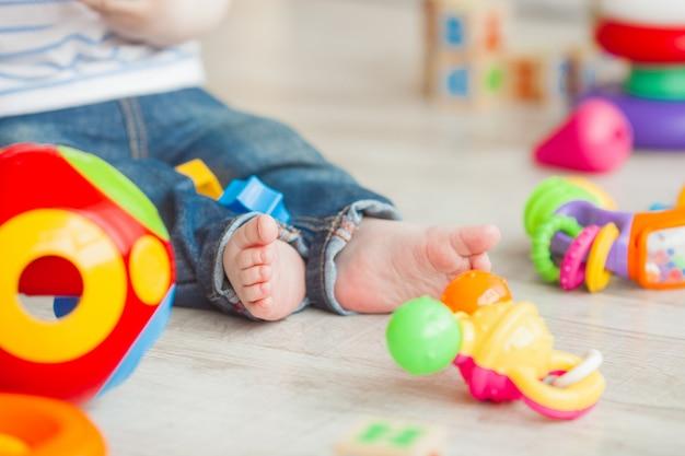 Неузнаваемый ребенок играет с красочными игрушками