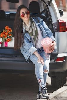 Молодая привлекательная женщина в машине с подарочной коробке, подарком и цветами. красивая дама в весеннее время с букетом тюльпанов. женщина в автомобиле.