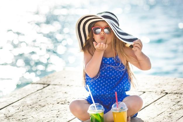 海の上のかわいい女の子。夏の帽子の少女。海岸線のかわいい子。