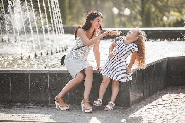 若い可愛い母と娘が噴水の近くで一緒に楽しんで。美しい女性と彼女の小さな子供がアイスクリームを食べます。楽しい陽気な家族。