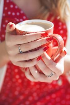 まだ若いコーヒーカップのクローズアップ。赤い色。
