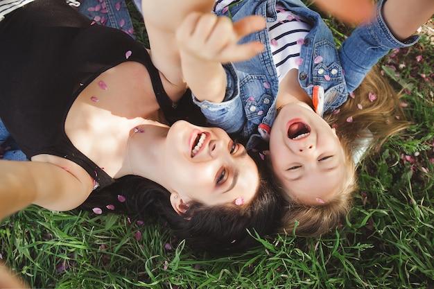 Молодая мать и ее дочь, принимая селфи