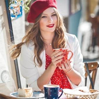 赤いベレー帽を着ている若い美しい女性のクローズアップの肖像画。