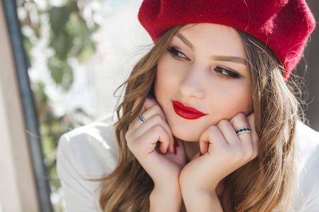 屋外の魅力的な若い女の子の肖像画。美しい都会の女性。赤い唇を持つ女性。
