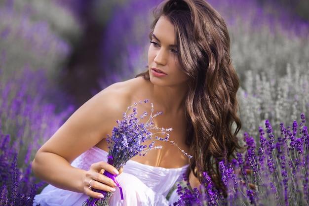 Крупным планом портрет красивой молодой женщины в сиреневом поле.