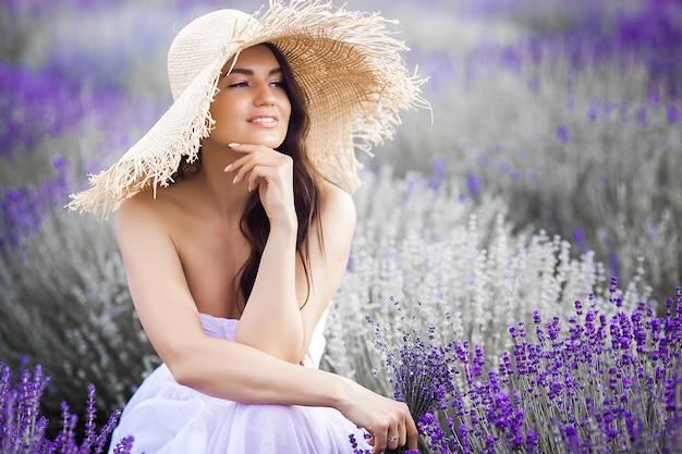 ラベンダー畑の美しい若い女性の肖像画を閉じます。