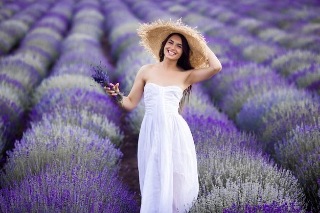 ラベンダー畑の若い美しい女性。夏の背景の女性