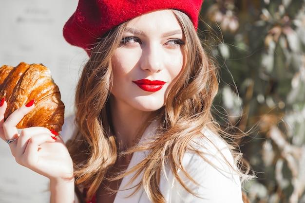 クロワッサンを食べる若い美しい女性のクローズアップの肖像画。フランス人の女の子。
