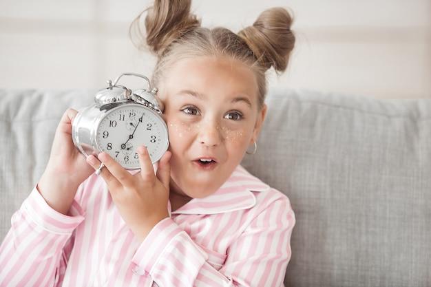 Время просыпаться. милая маленькая девочка с будильником