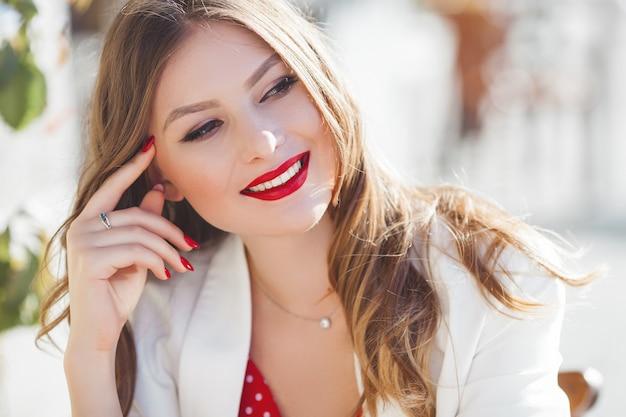 屋外の魅力的な若い女の子の肖像画。笑みを浮かべて美しい都市女性。赤い唇を持つ女性。