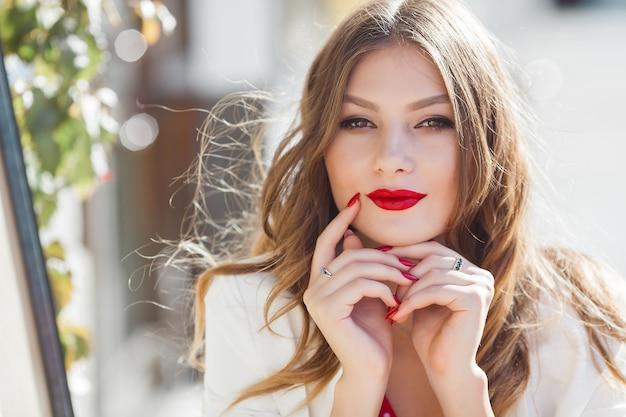 屋外の魅力的な若い女の子の肖像画。カメラを見て美しい都市の女性。赤い唇を持つ女性。