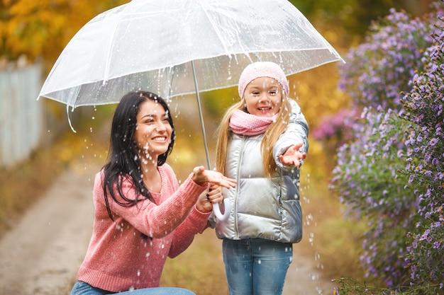 傘の下で秋に楽しんでいる若い母親とかわいい子。秋の陽気な家族