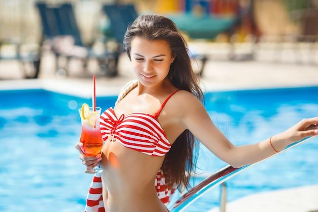 スイミングプールで非常に美しい若い女性