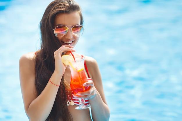 カクテルを飲んでスイミングプールで非常に美しい若い女性