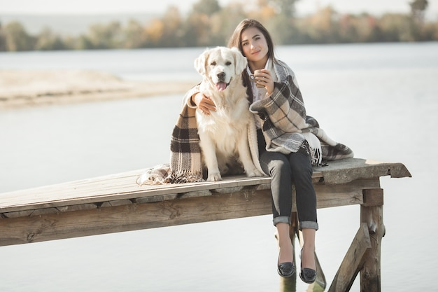 Молодая привлекательная женщина, сидя на пирсе со своей собакой. лучшие друзья на природе